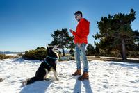 Mature man training dog in snow covered landscape 11015313864| 写真素材・ストックフォト・画像・イラスト素材|アマナイメージズ