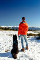 Rear view of man with dog looking out at snow covered landscape 11015313865| 写真素材・ストックフォト・画像・イラスト素材|アマナイメージズ