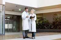 Two doctors having discussion, holding smartphone and diary 11015313927| 写真素材・ストックフォト・画像・イラスト素材|アマナイメージズ