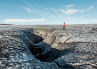Male tourist walking by glacial crevice, South Iceland 11015314004| 写真素材・ストックフォト・画像・イラスト素材|アマナイメージズ