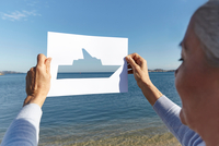 Senior woman standing facing the sea, holding out paper with cut-out of boat 11015314314| 写真素材・ストックフォト・画像・イラスト素材|アマナイメージズ