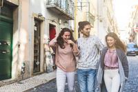 Three friends walking along street, Lisbon, Portugal 11015314377| 写真素材・ストックフォト・画像・イラスト素材|アマナイメージズ