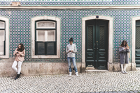 Three young adults standing in street, looking at their own smartphones, Lisbon, Portugal 11015314379| 写真素材・ストックフォト・画像・イラスト素材|アマナイメージズ