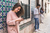 Three young adults standing in street, looking at their own smartphones, Lisbon, Portugal 11015314380| 写真素材・ストックフォト・画像・イラスト素材|アマナイメージズ
