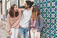 Three friends, standing in street, laughing, Lisbon, Portugal 11015314381| 写真素材・ストックフォト・画像・イラスト素材|アマナイメージズ