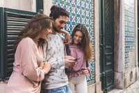 Three friends, standing in street, looking at smartphone, Lisbon, Portugal 11015314383| 写真素材・ストックフォト・画像・イラスト素材|アマナイメージズ