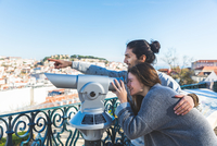 Young couple, sightseeing, looking through coin operated telescope, Lisbon, Portugal 11015314384| 写真素材・ストックフォト・画像・イラスト素材|アマナイメージズ