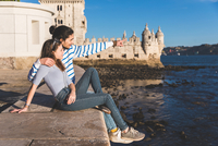Young couple sitting on wall by sea, Belem Tower in background, looking at view 11015314395| 写真素材・ストックフォト・画像・イラスト素材|アマナイメージズ