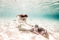 Female free diver swimming with stingray on seabed 11015314445| 写真素材・ストックフォト・画像・イラスト素材|アマナイメージズ