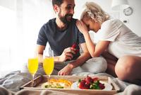 Couple sitting on bed, man proposing, holding open ring box 11015314539| 写真素材・ストックフォト・画像・イラスト素材|アマナイメージズ