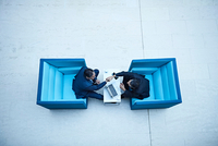 Overhead view of businessmen shaking hands in office atrium 11015315288| 写真素材・ストックフォト・画像・イラスト素材|アマナイメージズ