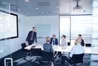 Businessman making flat screen presentation to team in boardroom 11015315364| 写真素材・ストックフォト・画像・イラスト素材|アマナイメージズ