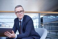 Portrait of confident businessman holding laptop on office balcony 11015315371| 写真素材・ストックフォト・画像・イラスト素材|アマナイメージズ