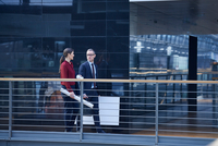 Businesswoman and man walking and talking on office balcony 11015315379| 写真素材・ストックフォト・画像・イラスト素材|アマナイメージズ