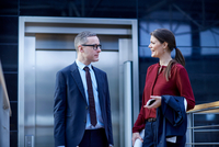 Businesswoman and man walking and talking on office balcony 11015315382| 写真素材・ストックフォト・画像・イラスト素材|アマナイメージズ