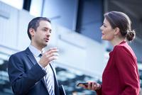 Businessman and woman talking in office atrium 11015315388| 写真素材・ストックフォト・画像・イラスト素材|アマナイメージズ