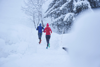 Rear view of male and female runners running on track in deep snow, Gstaad, Switzerland 11015315473| 写真素材・ストックフォト・画像・イラスト素材|アマナイメージズ