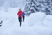Female and male runners running on track in deep snow, Gstaad, Switzerland 11015315474| 写真素材・ストックフォト・画像・イラスト素材|アマナイメージズ