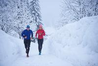Female and male runners running in falling snow, Gstaad, Switzerland 11015315477| 写真素材・ストックフォト・画像・イラスト素材|アマナイメージズ