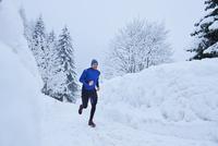 Male runner running on track in deep snow, Gstaad, Switzerland 11015315478| 写真素材・ストックフォト・画像・イラスト素材|アマナイメージズ