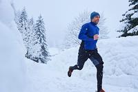 Male runner running on track in deep snow, Gstaad, Switzerland 11015315479| 写真素材・ストックフォト・画像・イラスト素材|アマナイメージズ