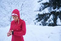 Female runner in red hoody checking smartwatch in snow, Gstaad, Switzerland 11015315481| 写真素材・ストックフォト・画像・イラスト素材|アマナイメージズ