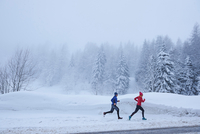 Distant view of female and male runners running in deep snow, Gstaad, Switzerland 11015315482| 写真素材・ストックフォト・画像・イラスト素材|アマナイメージズ