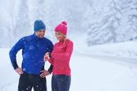 Female and male runners checking smartwatch on deep snow track, Gstaad, Switzerland 11015315492| 写真素材・ストックフォト・画像・イラスト素材|アマナイメージズ