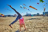 Young girl doing cartwheel on beach, kites flying in sky behind her, Rimini, italy 11015316379| 写真素材・ストックフォト・画像・イラスト素材|アマナイメージズ