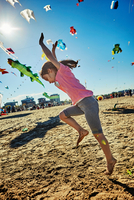 Young girl doing cartwheel on beach, kites flying in sky behind her, Rimini, italy 11015316380| 写真素材・ストックフォト・画像・イラスト素材|アマナイメージズ