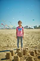 Portrait of young girl standing behind sand castles on beach, Rimini, italy 11015316381| 写真素材・ストックフォト・画像・イラスト素材|アマナイメージズ