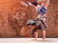 Dancer doing back flip, tiger street art in background 11015316448| 写真素材・ストックフォト・画像・イラスト素材|アマナイメージズ