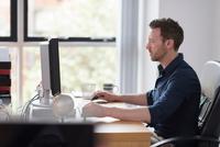 Man working at computer on office desk 11015316633| 写真素材・ストックフォト・画像・イラスト素材|アマナイメージズ