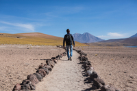 Man walking along path in sand in desert, San Pedro de Atacama, Chile 11015316776| 写真素材・ストックフォト・画像・イラスト素材|アマナイメージズ