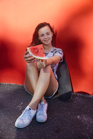 Teenage girl with watermelon and skateboard, red wall in background 11015316902| 写真素材・ストックフォト・画像・イラスト素材|アマナイメージズ