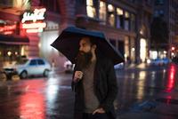 Mid adult man walking in city at night, using umbrella, Downtown, San Francisco, California, USA 11015317008| 写真素材・ストックフォト・画像・イラスト素材|アマナイメージズ