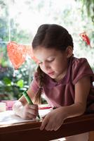 Girl sitting at window table drawing with crayon 11015317017| 写真素材・ストックフォト・画像・イラスト素材|アマナイメージズ