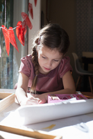Girl sitting at table concentrating on drawing 11015317018| 写真素材・ストックフォト・画像・イラスト素材|アマナイメージズ