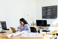 Woman sitting at desk in office working on laptop 11015317024| 写真素材・ストックフォト・画像・イラスト素材|アマナイメージズ