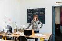 Portrait of woman in office looking at camera 11015317041| 写真素材・ストックフォト・画像・イラスト素材|アマナイメージズ