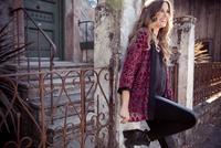 Stylish young woman leaning against front gateway 11015317138  写真素材・ストックフォト・画像・イラスト素材 アマナイメージズ