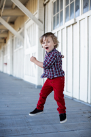 Portrait of cute boy jumping mid air on porch 11015317436| 写真素材・ストックフォト・画像・イラスト素材|アマナイメージズ