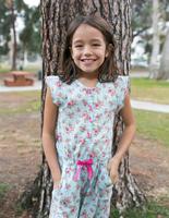 Girl posing against tree in park 11015317501| 写真素材・ストックフォト・画像・イラスト素材|アマナイメージズ