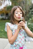 Girl blowing at dandelion on neighbourhood street 11015317504| 写真素材・ストックフォト・画像・イラスト素材|アマナイメージズ