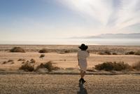 Rear view of woman wearing sunhat looking away at desert, Salton Sea, California, USA 11015317613| 写真素材・ストックフォト・画像・イラスト素材|アマナイメージズ