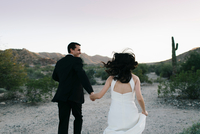 Bride and groom in arid landscape, holding hands, running, rear view 11015318000| 写真素材・ストックフォト・画像・イラスト素材|アマナイメージズ