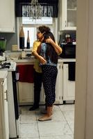 Grandmother hugging granddaughter in kitchen 11015318005| 写真素材・ストックフォト・画像・イラスト素材|アマナイメージズ