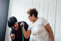 Woman helping senior woman to use resistance band 11015318038| 写真素材・ストックフォト・画像・イラスト素材|アマナイメージズ