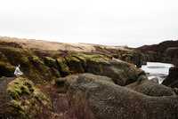 Man sitting on rock, looking at view, Iceland 11015318107| 写真素材・ストックフォト・画像・イラスト素材|アマナイメージズ