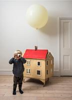 Boy standing beside dolls house looking through cardboard tube at camera 11015318141| 写真素材・ストックフォト・画像・イラスト素材|アマナイメージズ